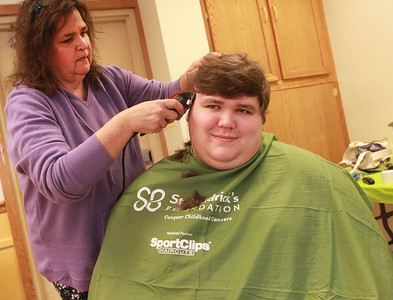 Candace H. Johnson-For Shaw Media  Tom Dawson, 20, of Antioch gets his head shaved by Patty Browning, of Island Lake, an independent hair stylist, during the St. Baldrick's Foundation event at the Fox Lake Volunteer Fire Department in Ingleside.  (3/15/20)