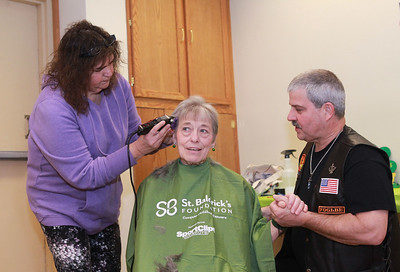 Candace H. Johnson-For Shaw Media  Sue Ryan, of Lake Villa, organizer, gets her hair cut by Patty Browning, of Island Lake, an independent hair stylist, as she holds hands for support with Bruce Preston, of McHenry during the St. Baldrick's Foundation event at the Fox Lake Volunteer Fire Department in Ingleside.  (3/15/20)