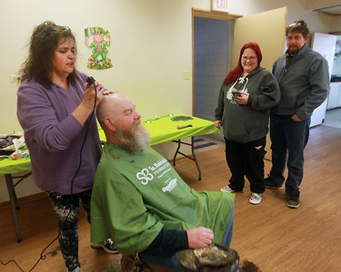 Candace H. Johnson-For Shaw Media  Patty Browning, of Island Lake, an independent hair stylist, works on John Calhoun, of McHenry as she shaves off his hair and beard while his daughter, Brittany, and Ian Crumley, both of Lake Geneva, Wis, stand by to support him during the St. Baldrick's Foundation event at the Fox Lake Volunteer Fire Department in Ingleside.  (3/15/20)