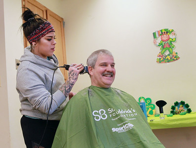Candace H. Johnson-For Shaw Media  Taylor Riemann, 23, of McHenry shaves her grandfather, Bruce Preston's, hair during the St. Baldrick's Foundation event at the Fox Lake Volunteer Fire Department in Ingleside.  (3/15/20)