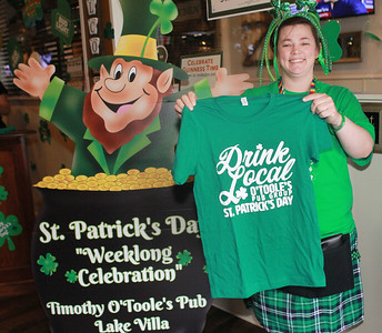 Candace H. Johnson-For Shaw Media Chandra Best, of Lake Villa holds up a t-shirt being sold to benefit the Alzheimer's Association during the St. Patrick's Day Weeklong Celebration on the weekend at Timothy O'Toole's Pub in Lake Villa.  (3/14/20)