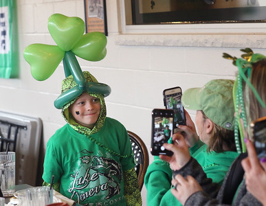 Candace H. Johnson-For Shaw Media Chason Maier, 10, of Iowa City, Iowa shows off his balloon hat made by leprechaun Peter O'Fool (Pete Kovacevich) as he gets his picture taken during the St. Patrick's Day Weekend Celebration at Timothy O'Toole's Pub in Lake Villa.  (3/14/20)