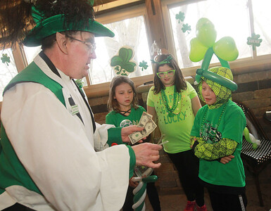Candace H. Johnson-For Shaw Media Leprechaun Peter O'Fool (Pete Kovacevich) does a magic trick using money as Gentry Maier, 8, of Iowa City, Iowa, Gianna Belluomini, 9, of Grayslake and Gentry's brother, Chason, 10, watch during the St. Patrick's Day Weekend Celebration at Timothy O'Toole's Pub in Lake Villa.  (3/14/20)