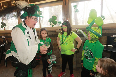 Candace H. Johnson-For Shaw Media Leprechaun Peter O'Fool (Pete Kovacevich) does a magic trick with money as Gentry Maier, 8, of Iowa City, Iowa, Gianna Belluomini, 9, of Grayslake, Gentry's brother, Chason, 10, and Gianna's sister, Chloe, 3, watch during the St. Patrick's Day Weekend Celebration at Timothy O'Toole's Pub in Lake Villa.  (3/14/20)