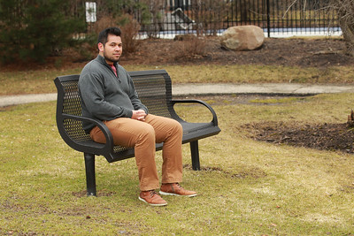 Candace H. Johnson-For Shaw Media Cody Delmendo, of Grayslake, a social care agent, sits on a bench in his apartment complex after he was laid off from Camping World a day earlier because of the Coronavirus (COVID-19).