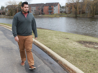 Candace H. Johnson-For Shaw Media Cody Delmendo, of Grayslake, a social care agent, walks near a pond in his apartment complex after he was laid off from Camping World a day earlier because of the Coronavirus (COVID-19).