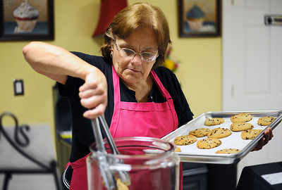 Sarah Nader - snader@shawmedia.com Employee Gail Wiser of McHenry stocks newly baked chocolate chip cookies while working at Sweet Angeline's Bake Shop and Gourmet Cafe in Richmond on Tuesday, May 1, 2012. The bakery opened last month in a renovated old farm house and features cupcakes, cakes, pastries, breads, soup and sandwich's.