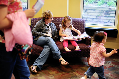 Sarah Nader - snader@shawmedia.com Janet Mathews (left) and her granddaughter, Kaylee Pease, 5, of Crystal Lake read their books during their weekly trip to the Crystal Lake Public Library on Wednesday, May 2, 2012. The library is planning a $28.6 million expansion that will more than double its current size.