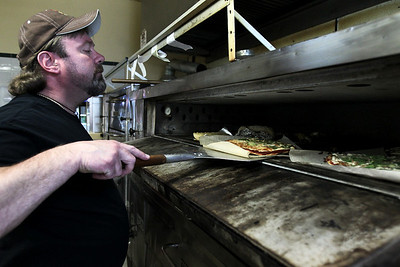 Sarah Nader - snader@shawmedia.com Fritz Larsen, owner of Stuc's Pizza in McHenry takes a pizza out of the oven on Friday, May 4, 2012. Larsen also owns Halftime Bar & Grill in  Johnsburg, Little Half Time Pizza in Richmond and is expanding his frozen pizza line which is on place to sell 115,000 pizzas this year.
