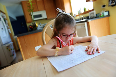 "Daniel J. Murphy - dmurphy@shawmedia.com  Miabella Carzoli, 5, works on a handwriting exercise at the kitchen table Tuesday May 15, 2012 in Woodstock. Her mother Tricia said, ""We decided it would be neat to teach our own children""."