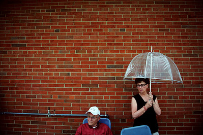 Daniel J. Murphy - dmurphy@shawmedia.com  Bruce (left) and Karen Black of Rockford seek shelter under a small overhang Tuesday May 15, 2012 at Harvard Junior High School during a lightning delay of the Class 1A Harvard Sectional semifinal.