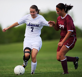 Daniel J. Murphy - dmurphy@shawmedia.com  Rockford Lutheran midfielder Bailey Peck (left) splits past Marengo's Emily Cisneros (right) in the first half Tuesday May 15, 2012 at Harvard Junior High School.Marengo fell to Rockford Lutheran 0-7 after a lightning delay.