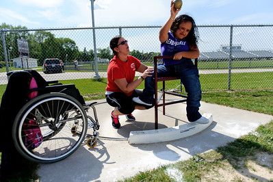 Daniel J. Murphy - dmurphy@shawmedia.com  Marengo Middle School teacher Trisha Bernstein (left) helps Liz Pitones, 18, of Marengo test out a custom chair that allows Liz to throw her shot put better Tuesday May 15, 2012 at Marengo High School. Liz's teammate Allison Rogutich decided to design and build the chair as an independent study project.