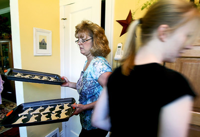 Sarah Nader - snader@shawmedia.com Diane Schuchert of Crystal Lake carries pans filled with Dachshund cut out cookies while preparing for the bake sale at the MidWest Dachshund Rescue Cross Town Bark Around Fundraiser at DuPage County Fairgrounds this Saturday.