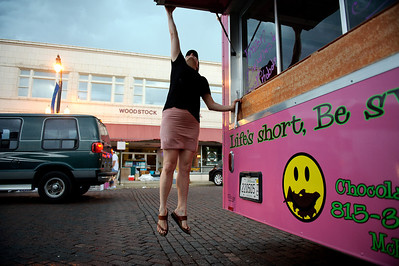 "Daniel J. Murphy - dmurphy@shawmedia.com  Tabitha Deibler of McHenry closes the awning on her ice cream stand in preparation of the aproaching storm Sunday May 20, 2012 in Woodstock. Vendors lined the Woodstock square Sunday for the 44th annual ""Fair Diddley"" craft show which benefits mental health related agencies in McHenry County."