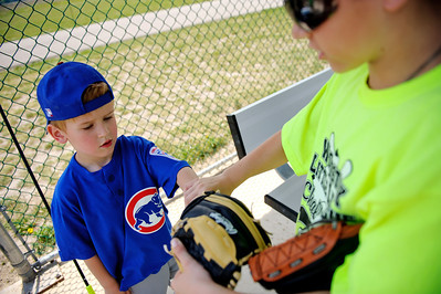 Daniel J. Murphy - dmurphy@shawmedia.com  Challenger Little League buddy Blake Shallenbager, 11, (right) helps Jacob Donahue, 9, (left) put on a helmut Sunday May 29, 2012 at Merryman Fields in Woodstock. The Challenger Little League division kicked off its season with opening ceremonies and games in Woodstock making it the first Little League program in northern McHenry County for young people with disabilities.