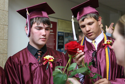 Mike Greene - mgreene@shawmedia.com Richmond-Burton student Jake Rymarz (left) receives a rose to give to his parents during graduation ceremonies for Richmond-Burton High School Sunday, May 20, 2012 in Richmond.