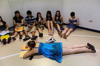 Daniel J. Murphy - dmurphy@shawmedia.com  Band member Delia Sargeant, 14, (center) passes the time by finishing her math homework during the 135th Commencement Ceremony Sunday May 20, 2012 at Woodstock High School.