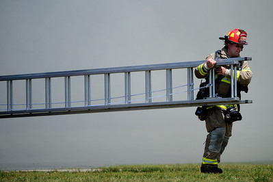 Daniel J. Murphy - dmurphy@shawmedia.com  A firefighter battles carries a ladder at the scene of a condominium fire at 1216 Walnut Glen Drive in Crystal Lake Thursday May 24, 2012