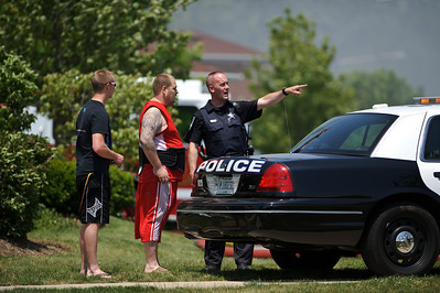 Daniel J. Murphy - dmurphy@shawmedia.com  A Crystal Lake police officer talks with onlookers at the scene of a condominium fire at 1216 Walnut Glen Drive in Crystal Lake Thursday May 24, 2012