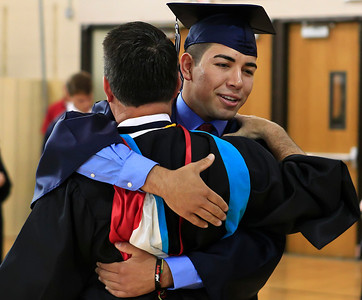 Brett Moist for the Northwest Herald Enrique Garcia, of Cary Grove, hugs the Dean of Students, Jim Kelly, to show his appreciation during the Senior Graduation Ceremony at Cary Grove High School on Saturday.