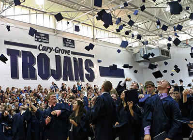 Brett Moist for the Northwest Herald Graduates throw their caps high into the air to celebrate during the Senior Graduation Ceremony at Cary Grove High School on Saturday.