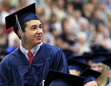 Brett Moist for the Northwest Herald Joshua Buckingham, of Cary Grove, looks up at his mom while she is being recognized for her contribution to the school during the Senior Graduation Ceremony at Cary Grove High School on Saturday.