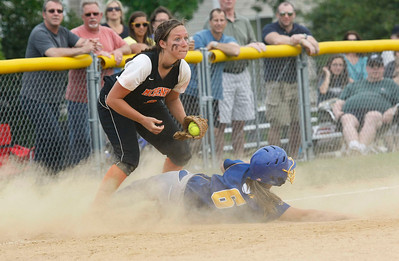 Candace H. Johnson – Shaw Suburban Media McHenry's Kara Ekx watches the field after making a late tag as Warren's Hayley Roane is safe on third in the fifth inning during the Class 4A Regional final at Warren Township High School in Gurnee.