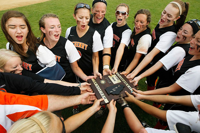 Candace H. Johnson – Shaw Suburban Media McHenry's varsity softball team huddle together with their championship plaque after beating Warren 6-2 during the Class 4A Regional final at Warren Township High School in Gurnee.