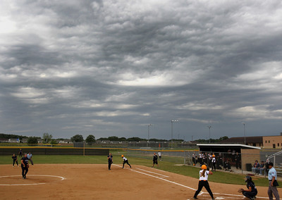 H. Rick Bamman - hbamman@shawmedia.com Cary Grove's Lindsay Efflandt pitches to Jacobs' Alyssa Lach in the first inning under threatning clouds during Saturday's  IHSA Class 4A Huntley regional softball game. The contest was suspended because of rain and lightning in top of third with two outs.