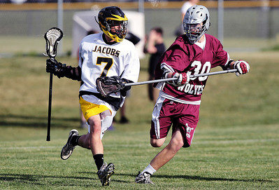 Sarah Nader - snader@shawmedia.com Jacobs' Shane Kathe (left) is guarded by Prairie Ridge's Jacob Beckman during Wednesday's NILAX semifinals in Algonquin on May 30, 2012. Jacobs won, 9-8.