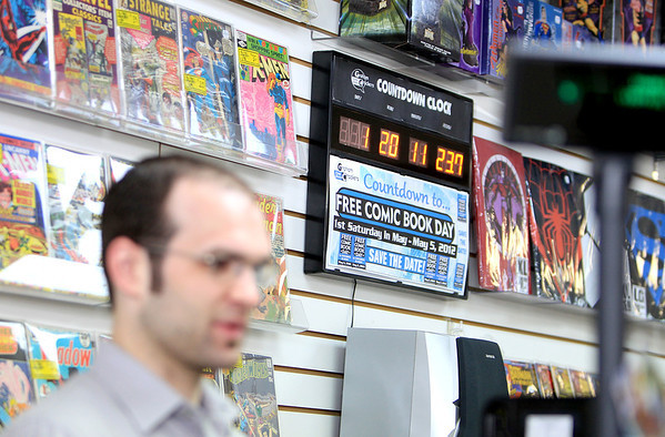 A countdown clock shows the amount of time left before Comic Book Store Day above the head of Graham Crackers Comics Store Manager Dan Weick Thursday. The St. Charles store will be participating in Commic Book Store today by giving away a selection of comics for free.