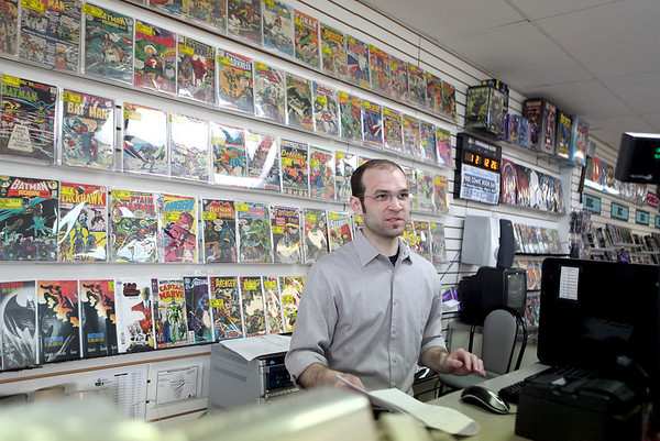 Dan Weick, store manager of Graham Crackers Comics on Randall Road in St. Charles, helps a customer Thursday. The store will be participating in Commic Book Store today by giving away a selection of comics for free.