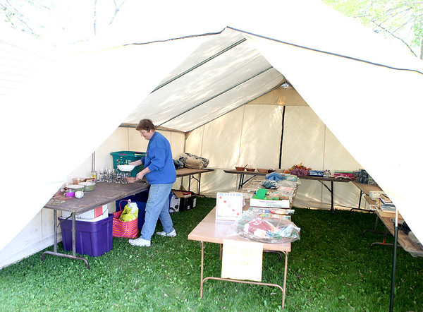 Barb Pinion sets up the things she hopes to sell during a village-wide garage sale this weekend in Maple Park. Pinion and her husband, Eric, will fill three tents in their yard with their goods.