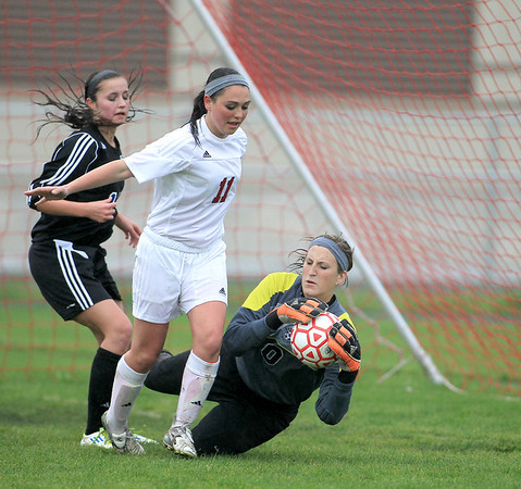 Batavia goalkeeper Roni Resek makes a save as Batavia's Lindsay Spears (center) and Geneva's Maggie Bodine look on during their game at Batavia Tuesday.