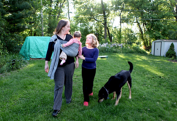 Amanda Littauer, holding 9-month-old daughter Lilah, walks through her Geneva backyard with 10-year-old daughter Zoë and dog Annie. Littauer and her partner, Laura Steele, have been together for 18 years.