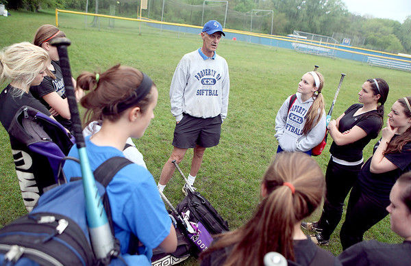 St. Francis softball coach Ralph Remus talks to his team, including his daughter, Maggie (bottom left), following practice at the school Monday.