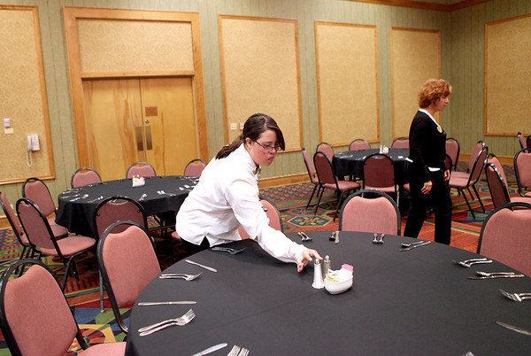 St. Charles East student Nikita Chavez places salt and pepper on a table in preparation for a luncheon for 450 guests at Pheasant Run Resort in St. Charles Wednesday morning. Chavez is a part of the school's community-based vocational training program.