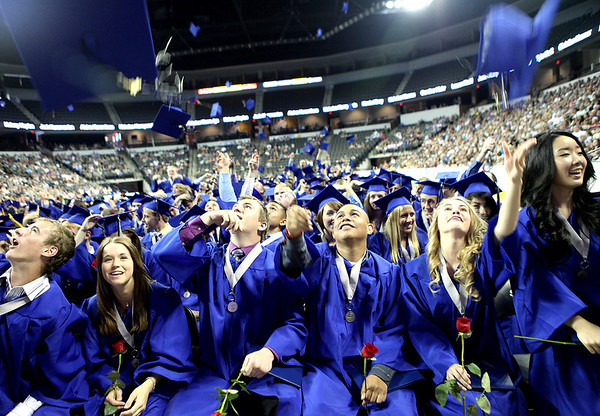 St. Charles North graduates toss their caps into the air following the school's commencement ceremony at the Sears Centre in Hoffman Estates Sunday afternoon.