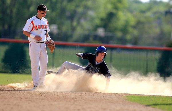 Jake Smiley of St. Charles North slides into second as St. Charles East's Nicholas Erickson looks on during their game at East Tuesday.