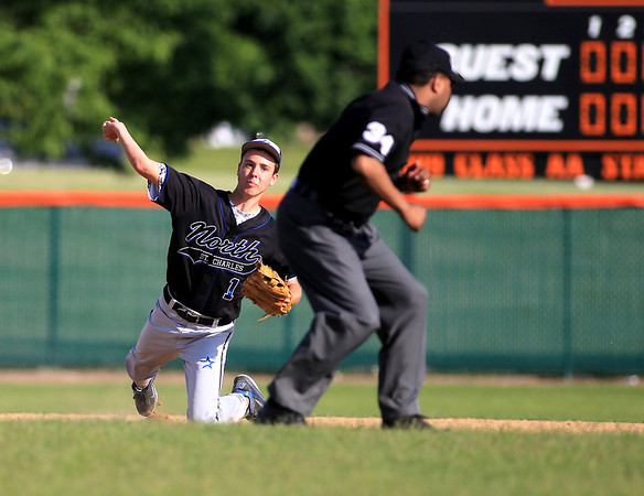 St. Charles North's Jake Smiley throws to first during their game at St. Charles East Tuesday.