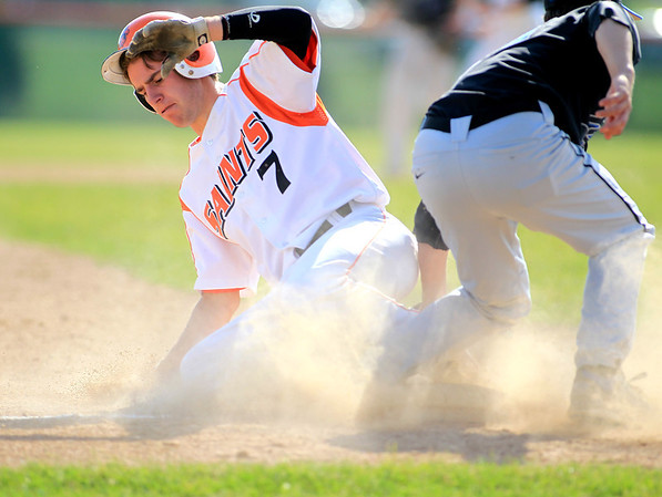 St. Charles East's Nick Huskisson slides into third under St. Charles North's John Brodner during their game at East Tuesday.