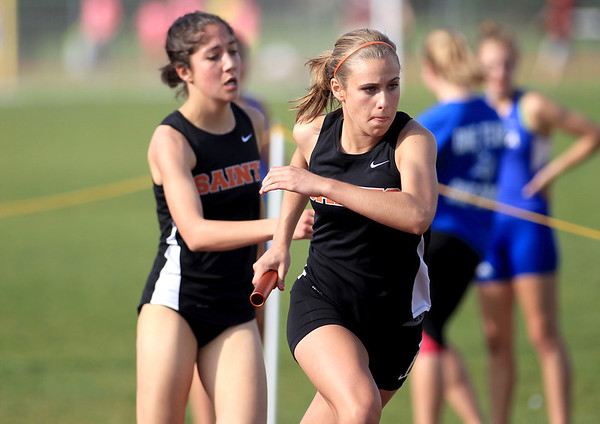 St. Charles East's Krista Rasmussen takes the handoff from teammate Sam Perez for the final leg of the 4 x 800 relay during the Upstate Eight River Division Girls Track and Field Championships at St. Charles North Thursday.