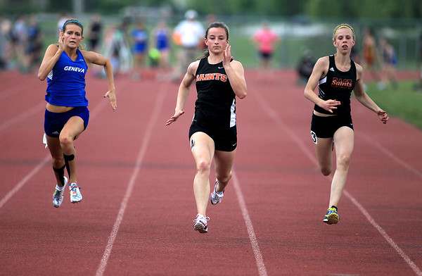 St. Charles East's Kelsey Gentry (center) cruises to a win in the 100-meter dash with Geneva's Mady Temple (left) and Allison Chmelik, also of St. Charles East, during the Upstate Eight River Division Girls Track and Field Championships at St. Charles North Thursday.