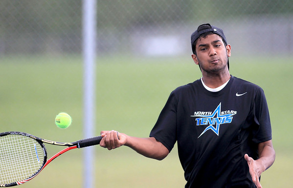 St. Charles North's Dom Amalraj returns the ball during No. 1 doubles play with partner Danny Oakes (not pictured) against St. Charles East's Connor Davis and Mike Muir Tuesday.