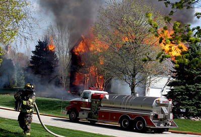 Sarah Nader -snader@shawmedia.com  Two firefighters are being treated for heat related injuries after four houses caught on fire Wednesday, May 1, 2013 in a Crystal Lake subdivision. One house is still on fire on the 3200 block of Carrington Drive in Crystal Lake. Firefighters are proceeding with caution because of a ruptured gas line.