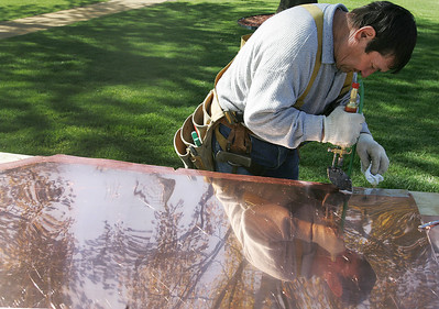 Kyle Grillot - kgrillot@shawmedia.com   Conrad Roofing of Illinois employee Joe Machaji prepares sheets of copper outside of St. John-Baptist Catholic Church. The church is under renovations as Conrad Roofing of Illinois installs a copper roof on the building. This project is estimated to take up to a year for completion.