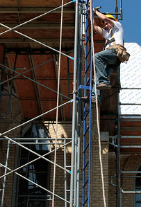 Kyle Grillot - kgrillot@shawmedia.com   Conrad Roofing of Illinois employee John Ramnski climbs down from the scaffolding around St. John-Baptist Catholic Church. The church is under renovations as Conrad Roofing of Illinois installs a copper roof on the building. This project is estimated to take up to a year for completion.
