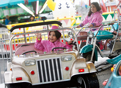 Candace H. Johnson Abigail Rainford, 4, of Spring Grove waves to her family with her sister, MacKenzie, 6, behind her as they enjoy a ride by Alpine Amusement during the Moose Fest Carnival at the McHenry Moose Lodge 691 in Johnsburg. The sisters were with their father, Scott, and grandparents, Ken and Tina Rainford, of Spring Grove.