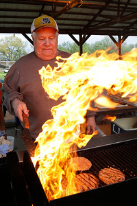 Candace H. Johnson Elmer Fritz, of McHenry, official chef, keeps his eyes on the flame while cooking hamburgers for the Moose Fest Carnival at the McHenry Moose Lodge 691 in Johnsburg.